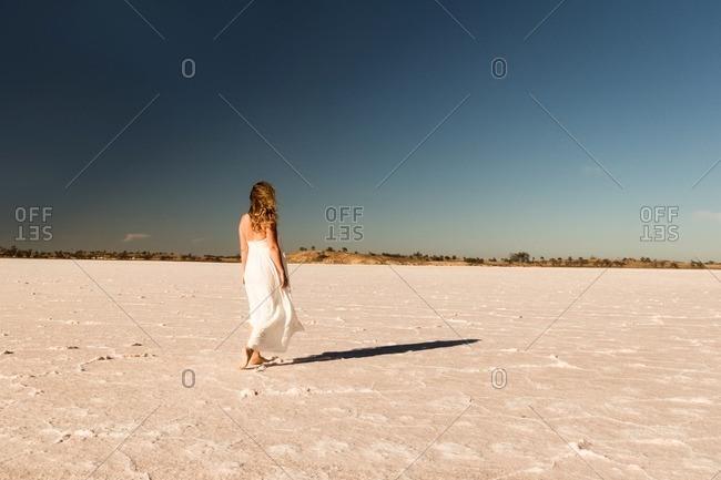 Woman in a white dress walking across a salt flat