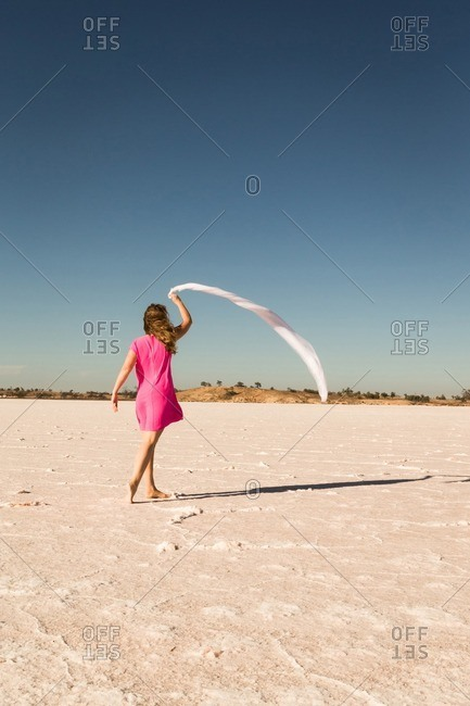 Woman in a pink dress walking across a salt flat with a scarf blowing in the wind