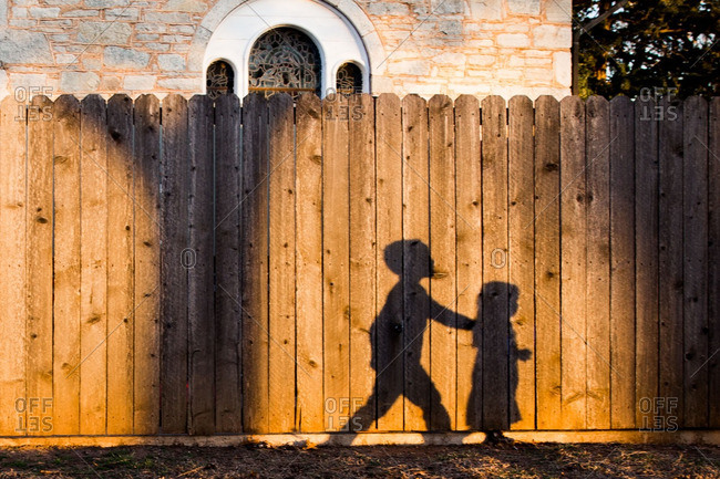 Shadow of two children on a fence