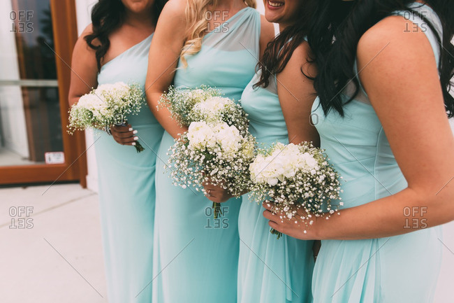 Bridesmaids in blue dresses holding bouquets with white flowers and baby's breath