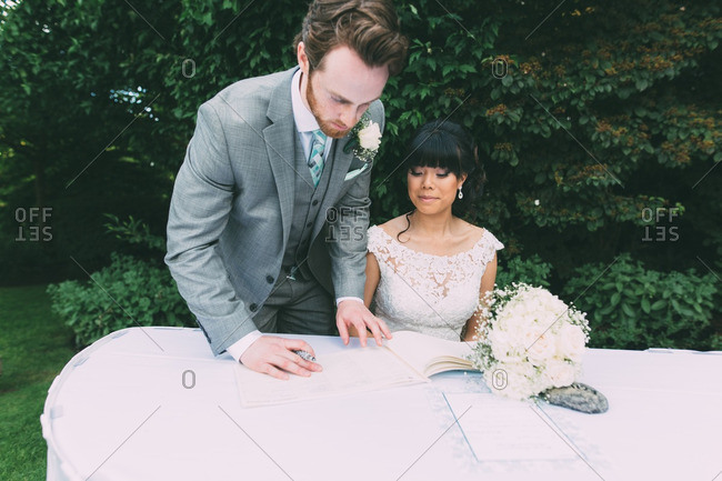 Newlywed couple signing the marriage certificate on their wedding day