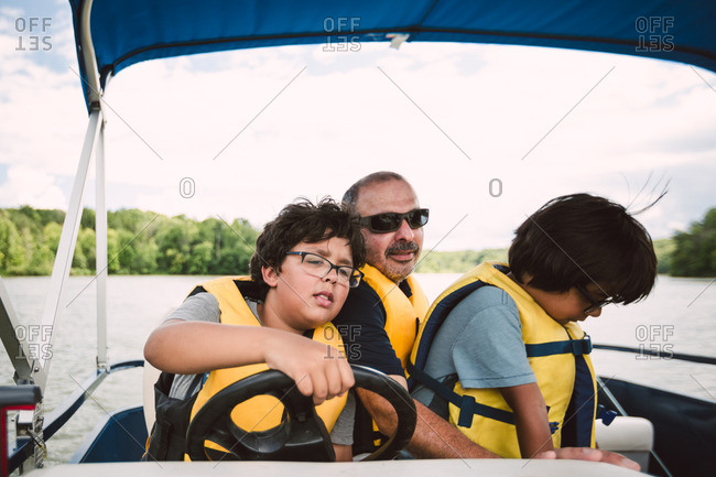 Father teaching his sons how to drive a boat
