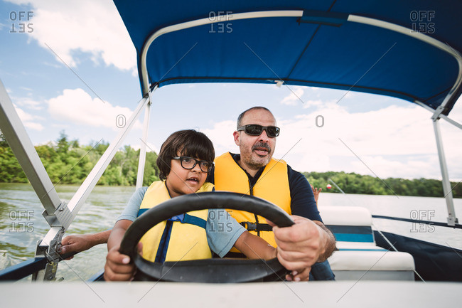 Father teaching son how to drive a boat