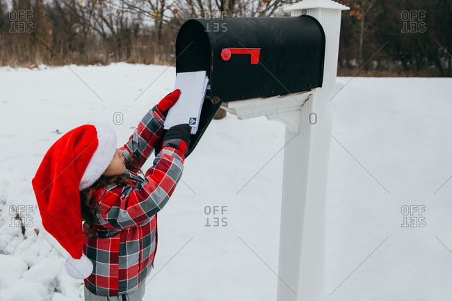 Little girl wearing a Santa hat getting mail from a mailbox