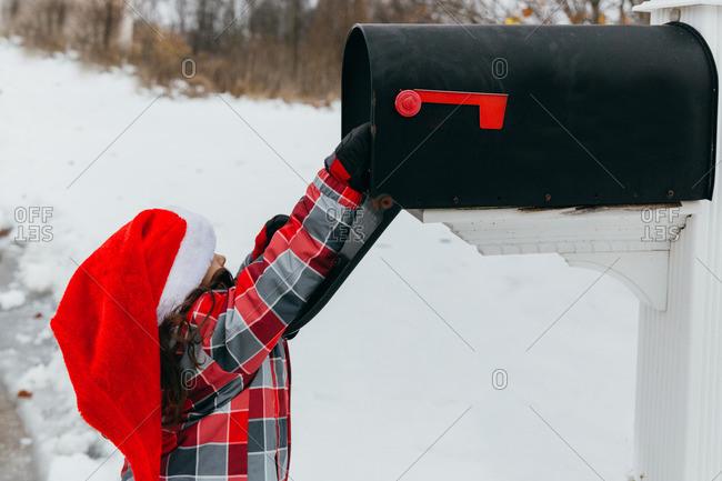 Little girl wearing a Santa hat reaching into a mailbox