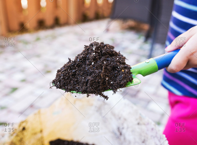 Child holding shovel filled with dirt
