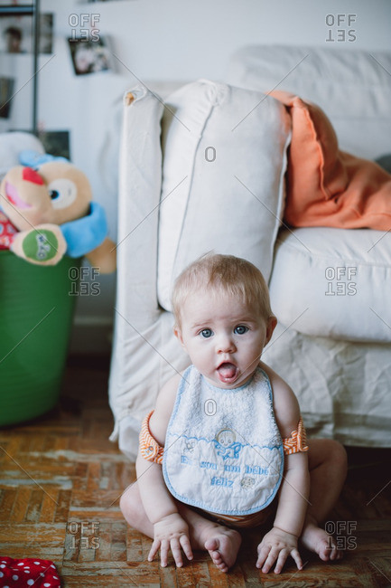 Portrait of baby in bib sitting on living room floor