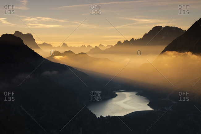 Orange light beam and mist on peaks of Dolomiti and Fedaia Pass, Cima Belvedere, Val di Fassa, Trentino-Alto Adige, Italy, Europe