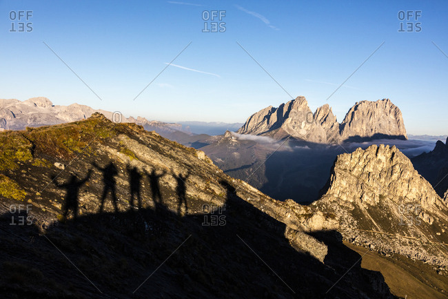 Silhouettes of hikers frame Sass Beca and Sassolungo from Cima Belvedere, Canazei, Val di Fassa, Trentino-Alto Adige, Italy, Europe
