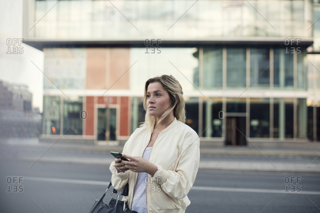 Young woman with mobile phone walking in city