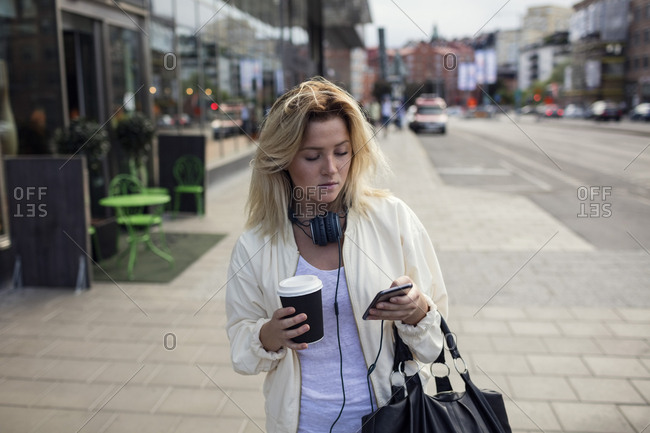 Young woman using smart phone while holding coffee cup on footpath in city