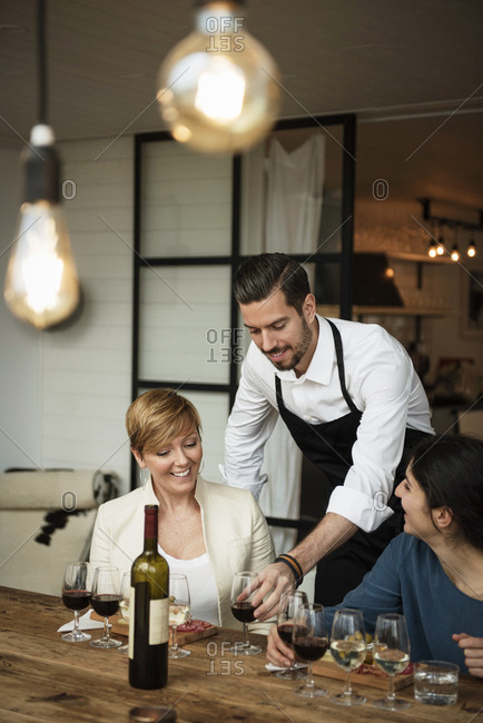 Smiling man wearing apron serving wine to businesswomen at table