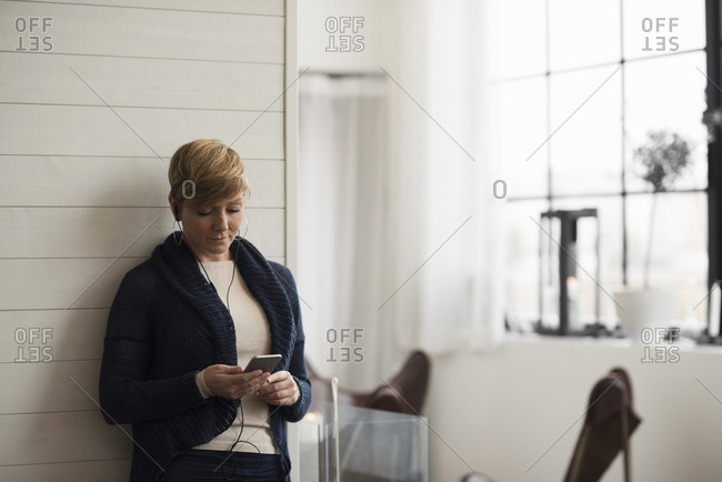 Business professional listening music though smart phone while leaning on wall at office