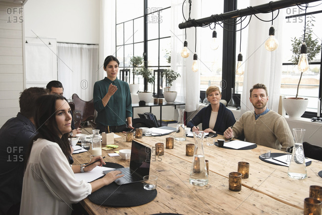Businesswoman explaining to colleagues during meeting at table in office