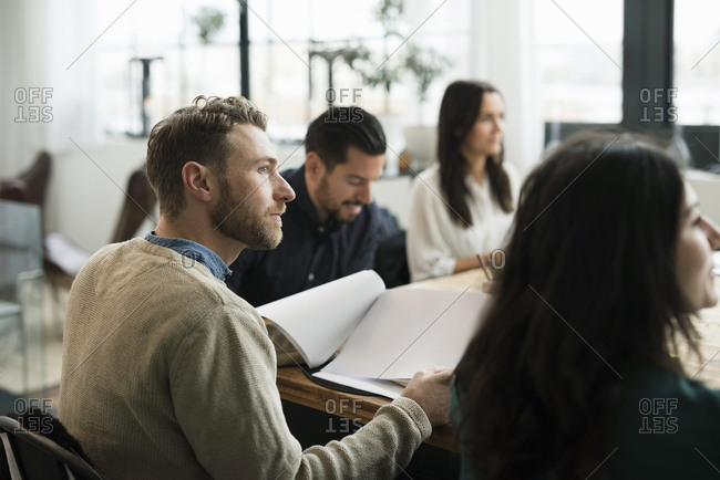 Business people listening during meeting at table in office