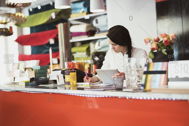 Female owner using digital tablet while writing on note pad at checkout counter in store