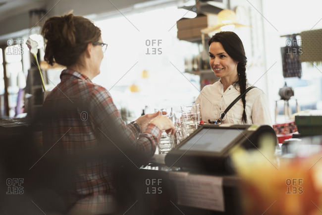 Owner showing drinking glasses to customer while standing at checkout counter in store