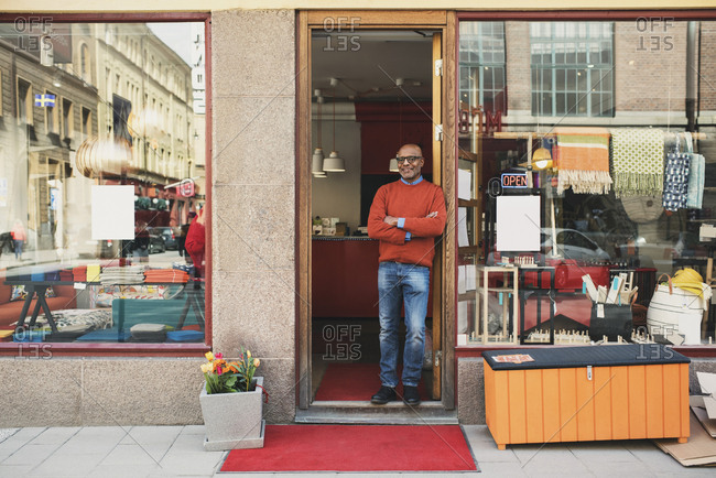 Full length of smiling owner standing at store entrance