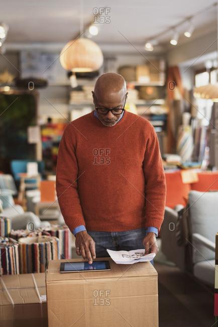 Senior man using digital tablet on box at store
