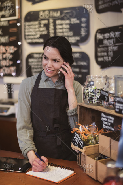 Smiling female owner using phone while writing in note pad at store counter