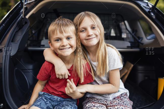 Portrait of happy girl and boy sitting in car trunk