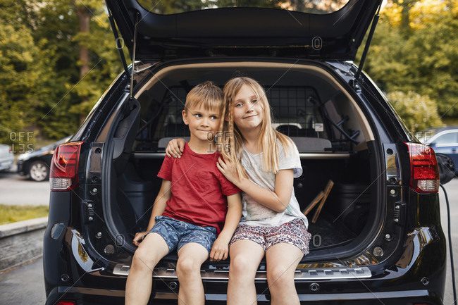 Portrait of happy girl sitting with brother in car trunk