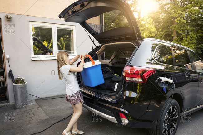 Girl loading cooler in black car trunk against house