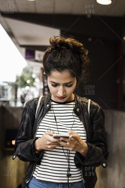 Woman listening music through smart phone in city
