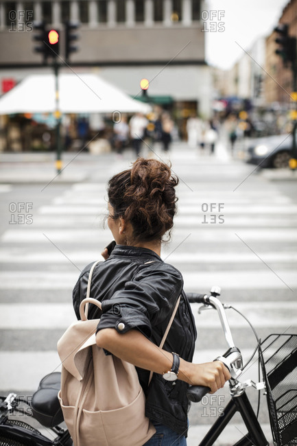 Woman with bicycle standing on zebra crossing in city