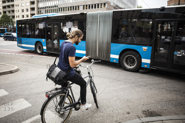 Man with bicycle using mobile phone while standing on city street against articulated bus