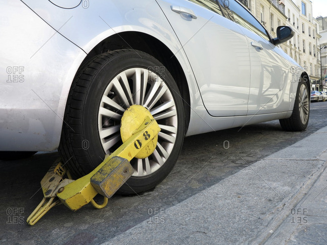 France, Paris. 8th district. Wheel clamp impeding parked car on a bus/taxis lane