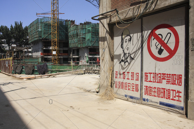Chine, Beijing - July 3, 2008: Chine, Beijing, Construction site and signs forbidding smoking and indicating the obligation to wear a helmet