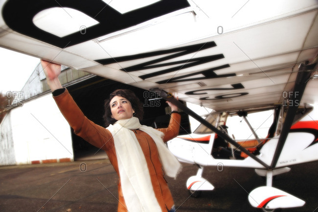 Pilot young woman checking the wing of her microlight.