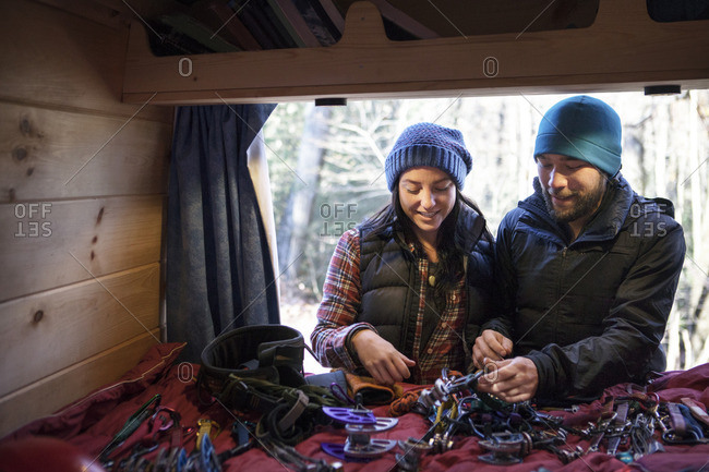 Couple looking at climbing equipment while standing by camper van