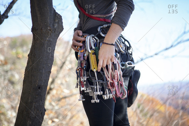 Midsection of woman with climbing equipment standing by tree trunk