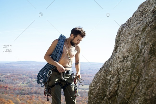 Man looking at climbing equipment while standing by rock formation