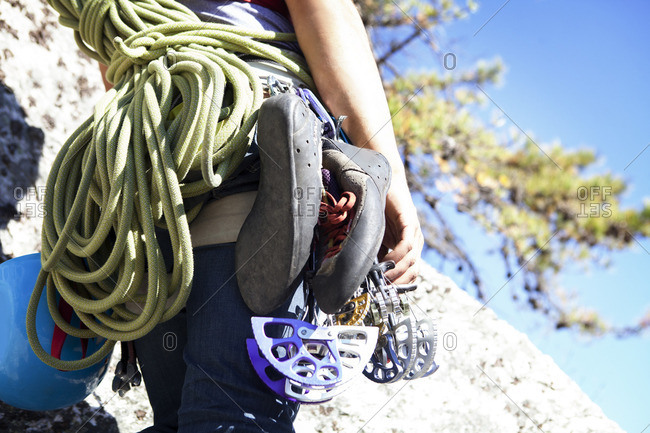 Midsection of woman with climbing equipment standing on rock