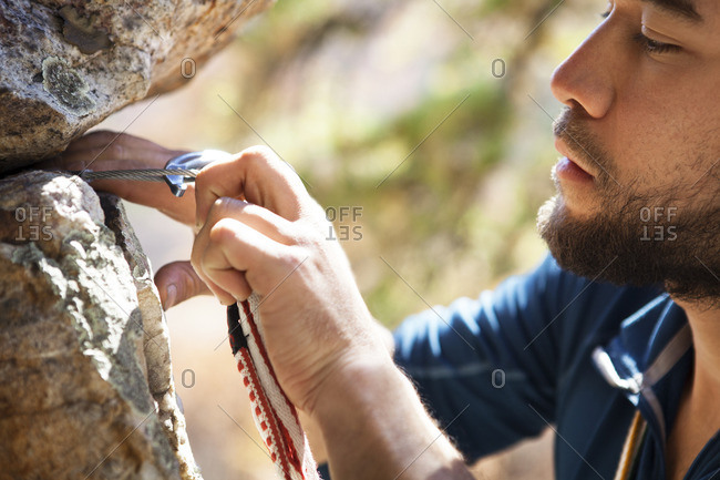 Cropped image of climber attaching carabiner on rocks