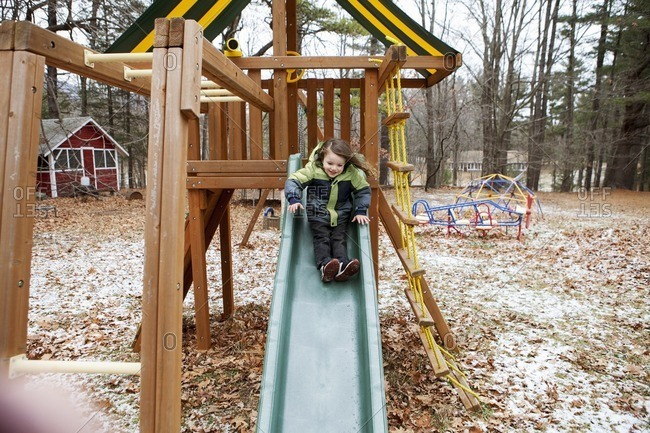 Full length of boy sliding on slide at park