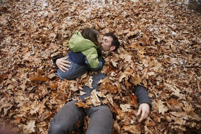 High angle view of father kissing son while lying in leaves