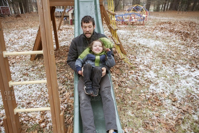 Father and son sliding on slide at park