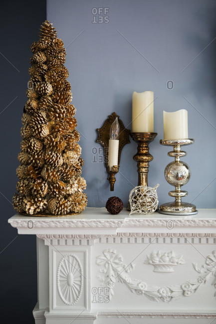 Christmas decoration and candles on mantelpiece