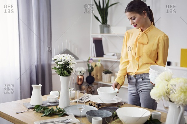 Smiling woman arranging dinning table at home