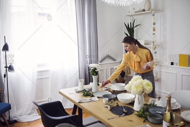 Woman arranging dinning table at home for party