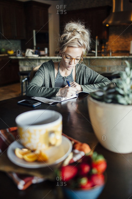 Woman writing diary while sitting at table