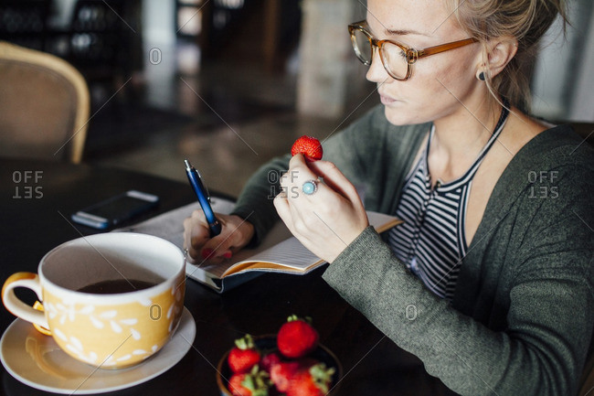 Woman with strawberry writing diary while sitting at table