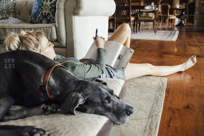 Woman writing diary while reclining on Great Dane