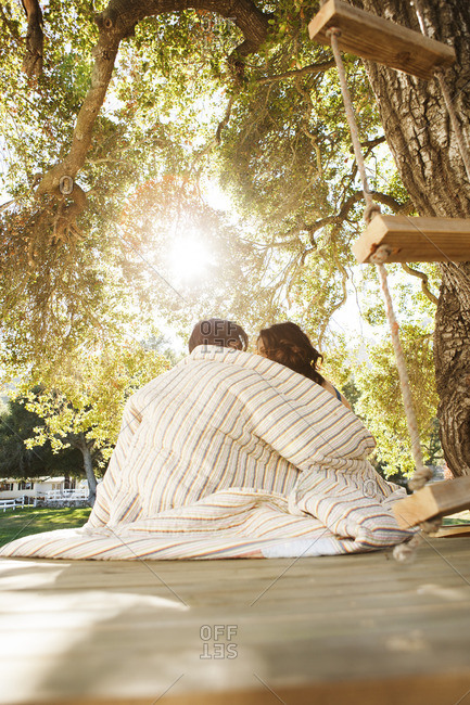 Couple covered in blanket relaxing on wooden seat at park