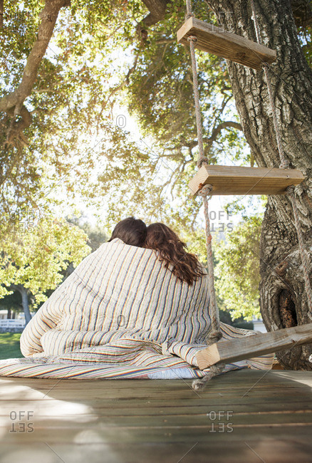 Romantic couple covered in blanket relaxing on wooden seat at park