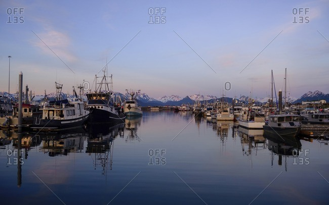 USA, Alaska, Homer - June 17, 2016: Boats moored in lake against snowcapped mountain during sunset